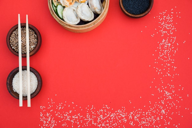 Dumplings in steamer with coriander seeds; black and white sesame seeds on red backdrop Free Photo
