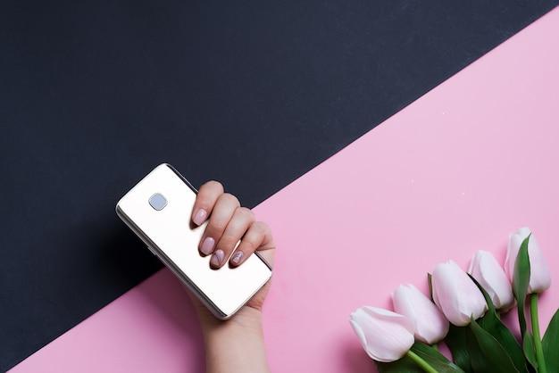 Карточка поздравления с мобильным телефоном в руке женщины и цветке белых тюльпанов весны на предпосылке диагонали duotone. Premium Фотографии