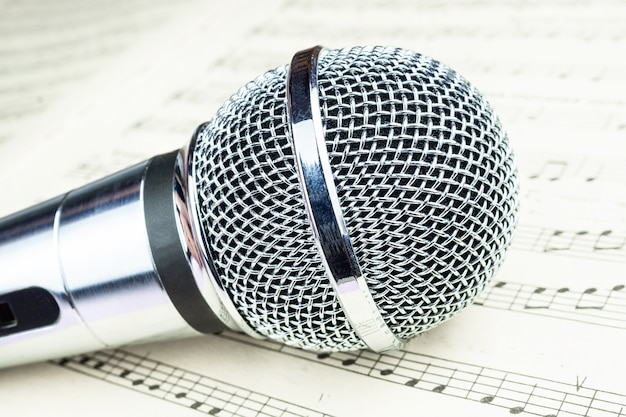 Dynamic microphone on music sheet Premium Photo
