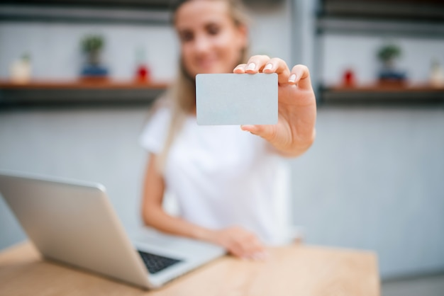 E-commerce concept. young woman holding a credit card. focus is on the card. Premium Photo