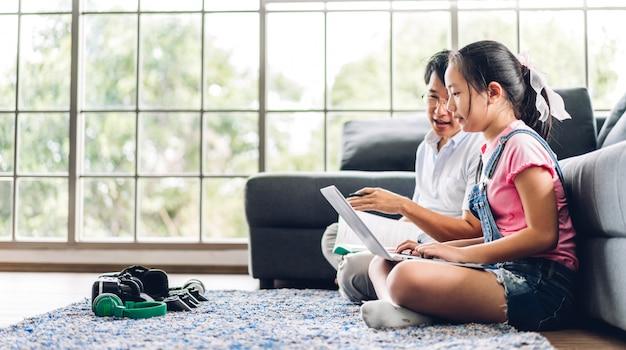 父とアジアの子供が小さな女の子の学習とオンライン教育eラーニングsystem.childrenビデオ会議で知識を勉強して宿題を作るラップトップコンピューターを見て自宅で家庭教師と Premium写真