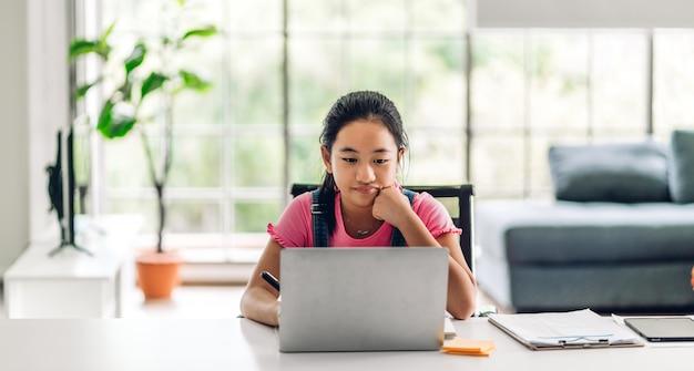 学校の子供が学習し、オンライン教育のeラーニングsystem.childrenビデオ会議で知識を勉強して宿題を作るラップトップコンピューターを見て自宅で先生の家庭教師と Premium写真