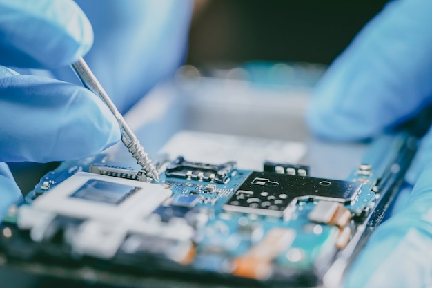 E-waste, technician repairing inside of mobile phone by soldering iron. Premium Photo