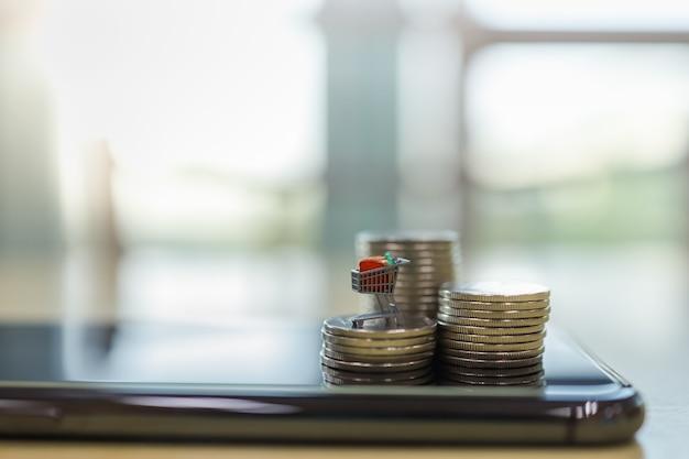 ビジネスeコマースとお金の概念。スマートな携帯電話の上にコインのスタックの上にショッピングカートまたはトロリーミニチュアフィギュアのクローズアップ Premium写真