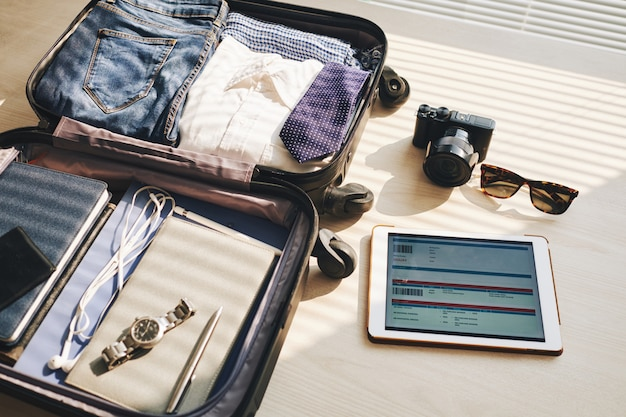 机の上のスーツケース、画面上のeチケット付きタブレット、カメラ、サングラス 無料写真