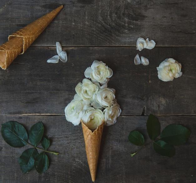 コーンの中のeアイスクリームボールスタイルで設定された白いバラ 無料写真