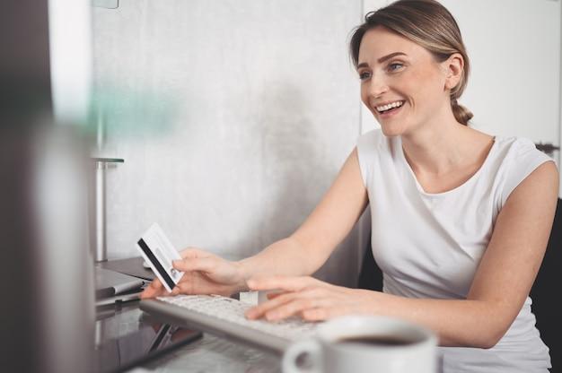 クレジットカードを手で押し、ラップトップコンピューターのキーボードを使用して美しい幸せな女。実業家や起業家が働いています。オンラインショッピング、eコマース、インターネットバンキング、お金の概念を使う Premium写真