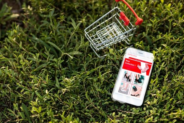 スマートフォンと緑の芝生のショッピングカート。環境のためのウェブサイト上のオンラインショッピングやeコマースのコンセプト。 Premium写真