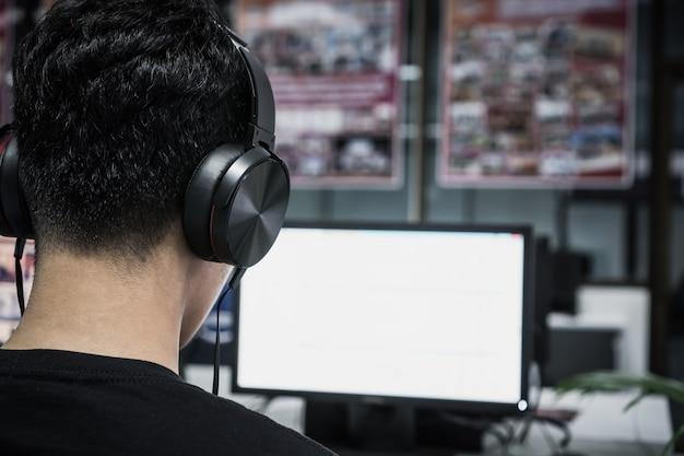 アジアの学生のための教育eラーニング外国語ヘッドフォンを身に着けている若い男 Premium写真