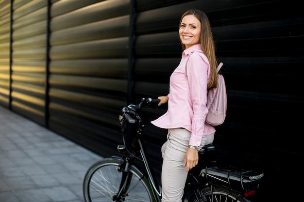 きれいな持続可能な都市交通として近代的な都市の電動eバイクを持つ若い女性 Premium写真