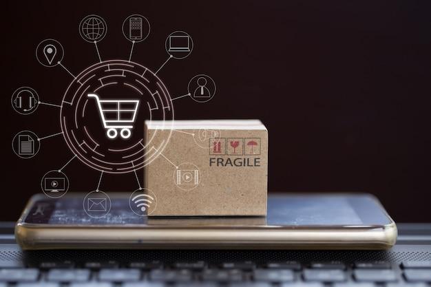 オンラインショッピング、eコマースの概念:ノートブックのキーボードとアイコンの顧客ネットワーク接続にスマートフォンを搭載した段ボール箱。インターネットに接続することによる製品サービスと消費者への配達。 Premium写真