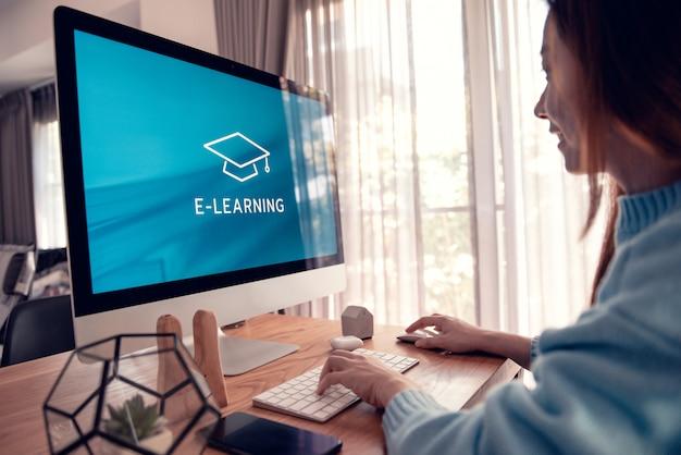 オンライン教育、eラーニング。若い女性はテーブルに座って、画面上の碑文とコンピューターモニターに取り組んで Premium写真