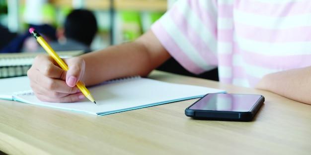 オンライン学習ホームスクールコンセプト、テーブルの上の大学生の手書きノートとスマートフォンのクローズアップ、大学教育とキャンパスでのコミュニケーション、ホームスクールオンライン教育、eラーニング Premium写真