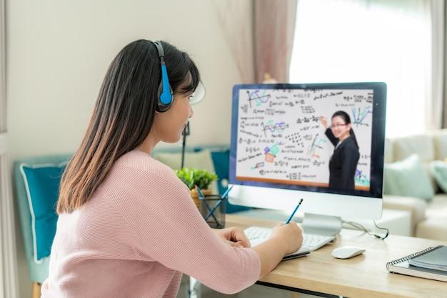 アジアの女性学生ビデオ会議eラーニングと自宅のリビングルームのコンピューター上の教師。 Premium写真