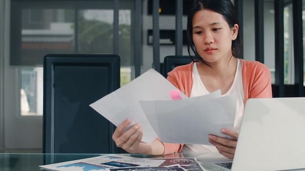 若いアジア妊婦の自宅での収入と支出の記録。ラップトップの記録予算、税、財務書類、自宅のリビングルームで働くeコマースを使用して幸せなママの女の子。 無料写真