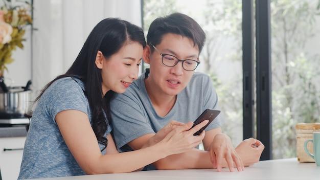 アジアの若いカップルは、自宅の携帯電話でオンラインショッピングをお楽しみください。ライフスタイルの若い夫と妻は、午前中に家のモダンなキッチンで朝食を食べた後、eコマースを購入します。 無料写真