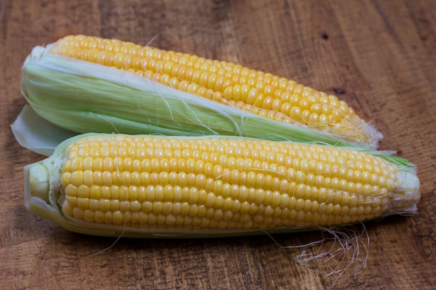 An ear of corn isolated on a wooden background Free Photo