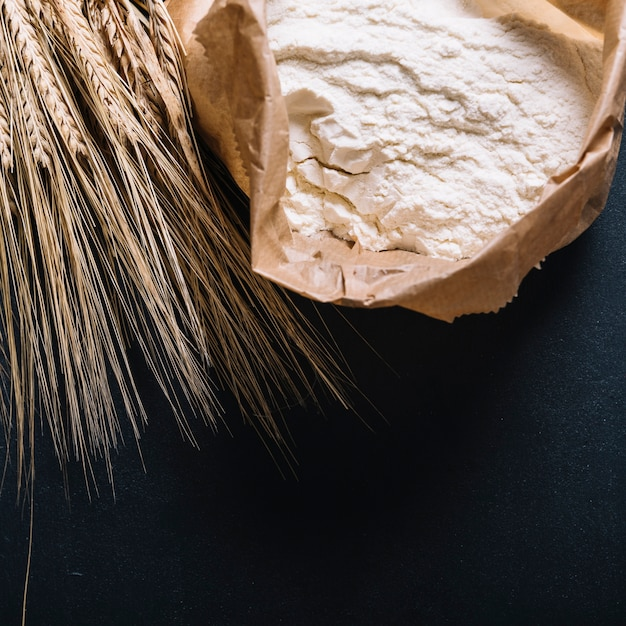 Ear of wheat and flour in paper bag on black background Free Photo