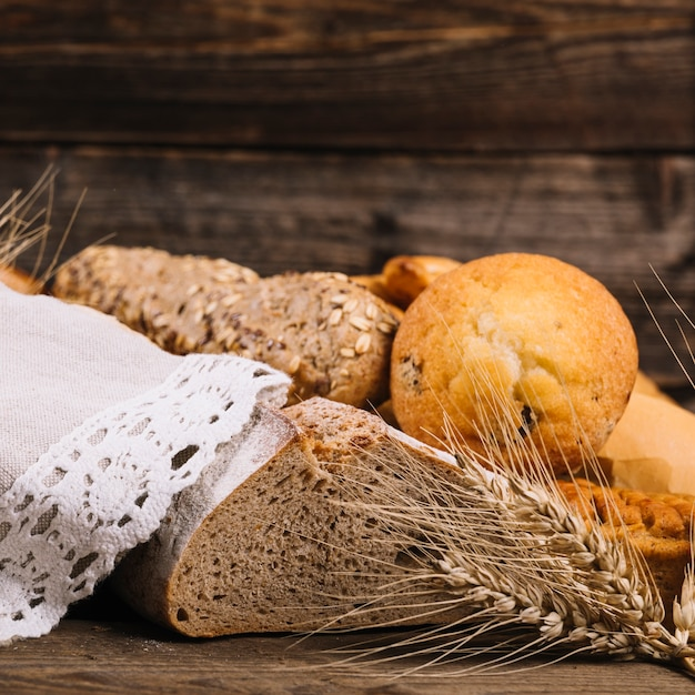 Ear of wheat with baked bread on wooden table Free Photo