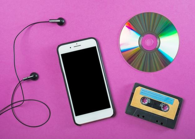 Наушники; сотовый телефон; компакт-диск и кассетная лента на фиолетовом фоне Бесплатные Фотографии