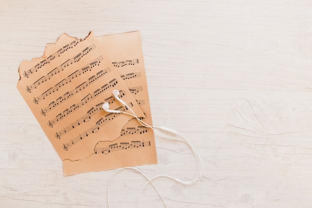 Earphones near sheet music Free Photo