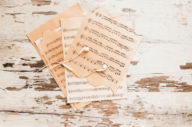 Earphones and sheet music on crumbling tabletop Free Photo