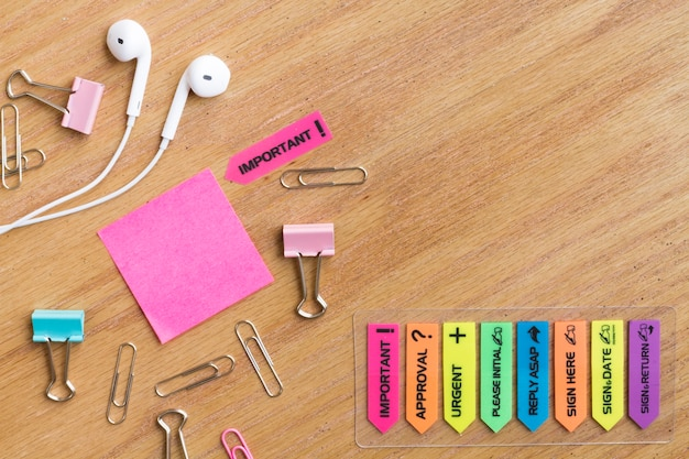Earphones with stationery located on wooden table Free Photo