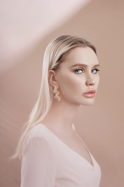 Earrings and jewelry in ear of a sexy blonde woman Premium Photo