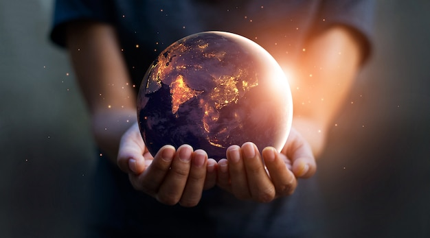 Earth at night was holding in human hands. earth day. energy saving concept. Premium Photo