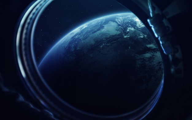 Earth in the porthole of space station. Premium Photo
