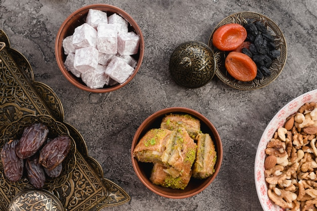 Earthen bowl of lukum; baklava; dates; nuts and dried fruits on gray concrete Free Photo