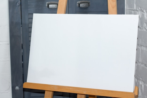An easel with a clean white canvas is ready for work against a white brick wall Premium Photo