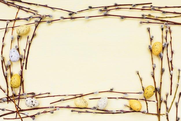 イースターの背景。柳の枝と装飾的な黄色の卵の境界線。コピースペース、トップビュー Premium写真