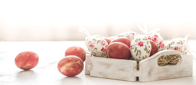 Easter background with a basket and red eggs with flowers Free Photo