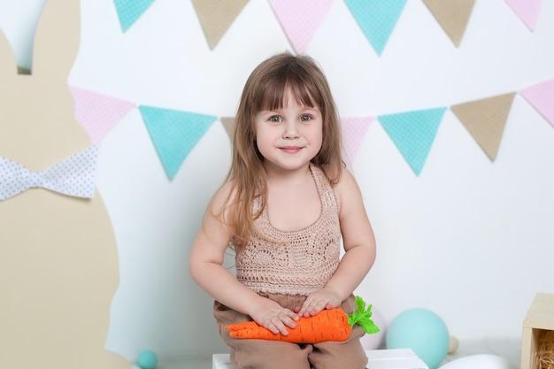 Пасхальный! красивая маленькая девочка на белизне с морковью. семейные праздники, традиции. сбор урожая, маленький фермер. сельское хозяйство. пасхальный декор, весенние украшения. овощи, веганские, вегетарианские Premium Фотографии