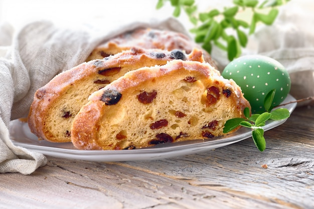 Easter bread, close-up on traditional fruty bread on rustic wood with fresh leaves and painted egg Premium Photo