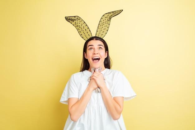 黄色のスタジオで明るい感情を持つイースターバニーの女性 無料写真