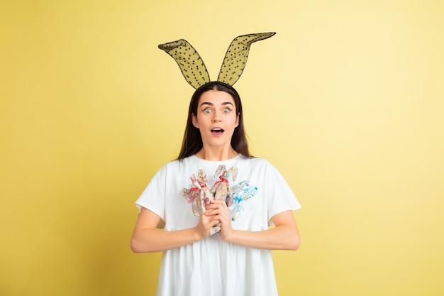 노란색 벽에 밝은 감정을 가진 부활절 토끼 여자 무료 사진