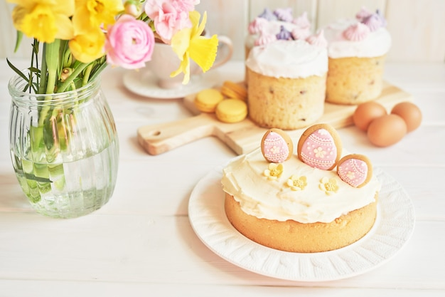 Easter cakes on table, macaroons, eggs and bouquet of flowers in vaseaster Premium Photo