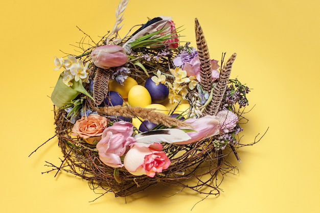 Easter card. painted easter eggs in nest on yellow Free Photo