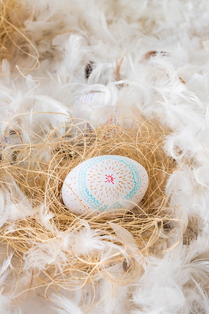 Easter chicken egg on hay between heap of feathers Free Photo