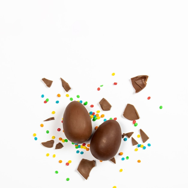 Easter chocolate eggs and colorful decorations on a light surface. easter concept, easter treats. square. flat lay, top view Premium Photo