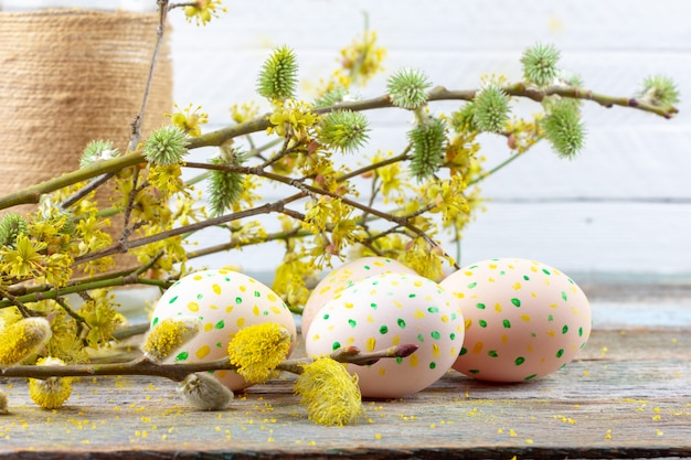 Easter composition of blooming willow twigs, dogwoods and easter eggs with a pattern of yellow and green dots on a wooden retro background space close-up Premium Photo