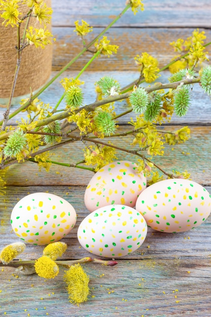 Easter composition of blooming willow twigs, dogwoods and easter eggs with a pattern of yellow and green dots on a wooden retro background space closeup Premium Photo