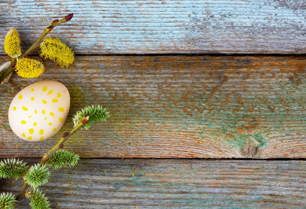 Easter composition of blooming willow twigs and easter eggs with a pattern of yellow dots on a wooden retro background with copy space top view close-up Premium Photo