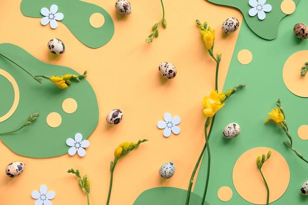緑と黄色のイースター構成。ウズラの卵、フリージアの花とフラットレイ、上面図。 Premium写真