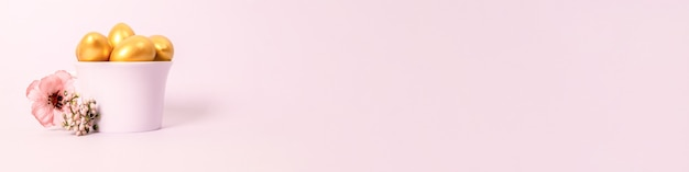 도자기 컵에 황금 장식 달걀과 분홍색 배경에 꽃의 부활절 구성. 선택적 초점, 복사 공간. 프리미엄 사진