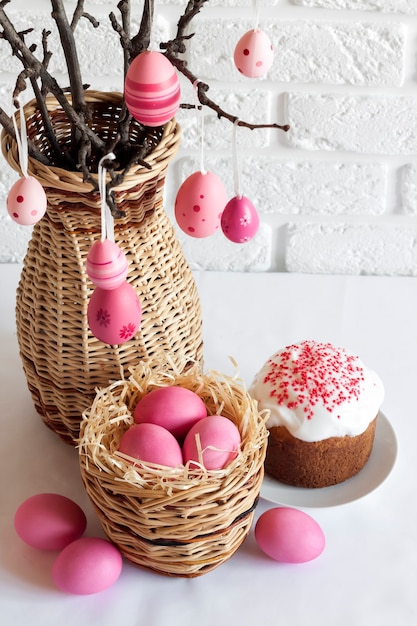 Easter composition with decorated tree branches in a wicker vase, pink colored eggs in wicker basket and easter cake on white background. copy space Premium Photo