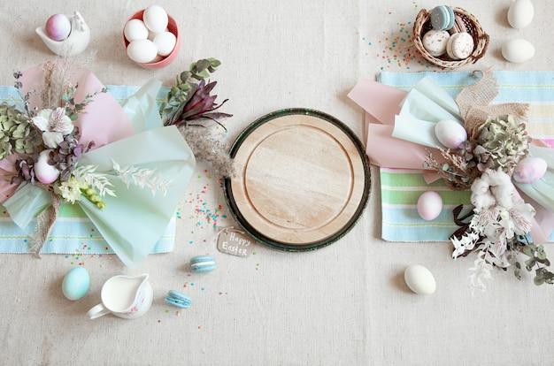 花、卵、パステルカラーのテキスト用の木製スペースが平らに置かれたイースターの構成。 無料写真