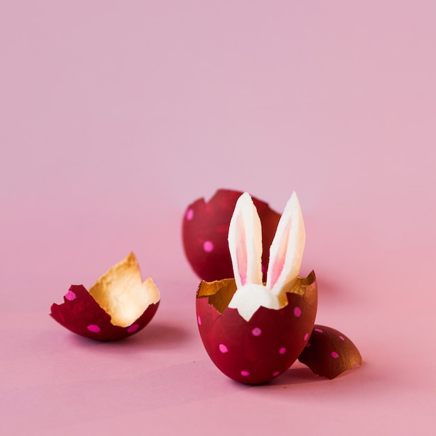 Easter concept. colored eggs on pink background, easter bunny hiding Premium Photo